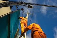 Salita asiatica dell'elettricista alta sul palo per riparare sistema elettrico Fotografia Stock