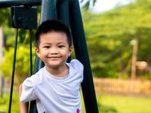 Salita cinese del ragazzo del bambino sulle oscillazioni fotografia stock libera da diritti