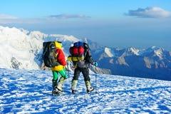 Salita dell'alpinista al picco di alta montagna Immagini Stock