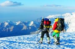 Salita dell'alpinista al picco di alta montagna Fotografia Stock