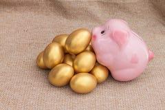 Salita rosa del porcellino salvadanaio sul mucchio dell'uovo di Pasqua dorato Immagini Stock