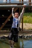 Salite dell'uomo sulle barre sopra acqua Corsa di eroi Fotografia Stock