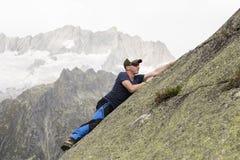 Salite dello scalatore su una parete pendente della roccia nelle montagne svizzere Fotografia Stock