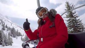 Salite dello sciatore della donna sulla seggiovia alla cima della montagna e della mano d'ondeggiamento archivi video