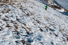 Salite di viaggiatore con zaino e sacco a pelo sul picco di montagna Immagini Stock