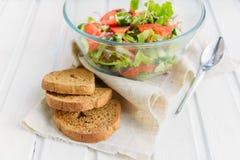 Sallad av den grönsallatbladet, tomaten, gurkan, löken, oreganon med olivolja och citronen Arkivbild