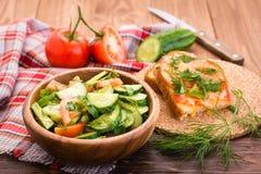 Sallad av gurkor och tomater i en träplatta, bakade smörgåsar med ost och grönsaker på en tabell Royaltyfri Fotografi