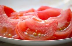 Sallad av mogna röda saftiga tomater i ett plattaslut upp Arkivbild