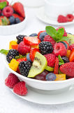 Sallad av ny frukt och bär i en vit bunke, närbild Arkivbilder