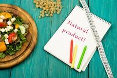 sallad av nya grönsaker, måttbandet och notepaden med text & x22; Naturprodukt! & x22; Fotografering för Bildbyråer