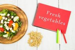 sallad av nya grönsaker och notepaden med text & x22; Ny vegetables& x22; Arkivbild
