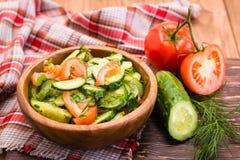 Sallad av tomater och gurkor i en platta och grönsaker på en trätabell Fotografering för Bildbyråer
