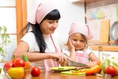Sallad för danande för moderundervisningbarn i kök Mamma och unge som hugger av grönsaken på skärbräda med kniven Matlagningbegre Royaltyfri Bild