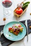 Sallad för ny grönsak i en blå platta och ett exponeringsglas av vin arkivbild