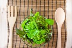 Sallad för ny grönsak med den gröna eken och raket med den träskeden och gaffeln royaltyfri fotografi