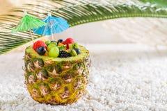 Sallad för nya frukter i ananas med coctailparaplyer på stranden Royaltyfri Bild