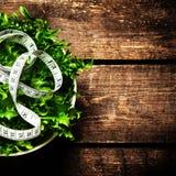 Sallad för viktförlust och mätaband över träbakgrund Di Fotografering för Bildbyråer