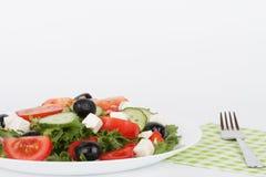 Sallad grec traditionnel avec l'olive noire du plat blanc sur le petit morceau Images stock