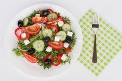 Sallad grec traditionnel avec l'olive noire du plat blanc sur le petit morceau Photos stock