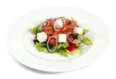 Sallad Grek på en vit bakgrund Medelhavs- med Fetaost, tomater och oliv Arkivfoton