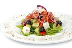 Sallad Grek på en vit bakgrund Medelhavs- med Fetaost, tomater och oliv Royaltyfri Foto