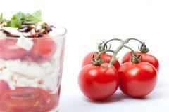 Sallad i exponeringsglas med tomater, fetaost och ny basilika Royaltyfri Bild