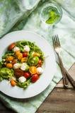 Sallad med arugula, tomater och mozarella på träbakgrund Arkivfoton