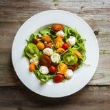Sallad med arugula, tomater och mozarella på träbakgrund Fotografering för Bildbyråer