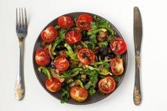 Sallad med aubergine och körsbärsröda tomater på en mörk platta på en vit bakgrund, bästa sikt Arkivfoto