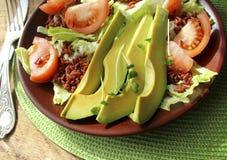Sallad med avokadot, tomater, grönsallat, ris Royaltyfri Bild