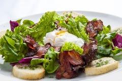 Sallad med bacon och det tjuvjagade ägget på en vit platta arkivfoton