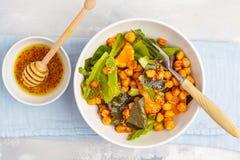 Sallad med bakade pumpa och kikärtar med senap-honung dressi Arkivfoton