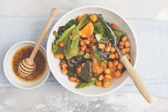 Sallad med bakade pumpa och kikärtar med senap-honung dressi Arkivbild