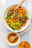 Sallad med bakade pumpa och kikärtar med senap-honung dressi Royaltyfri Foto