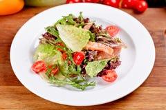 Sallad med den rökt laxen, tomater, grönsallat och arugula på den vita plattan fotografering för bildbyråer