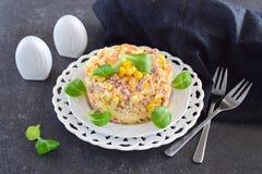Sallad med den rökte korven, havre, ost, den nya moroten, ägget, vitlök och yoghurt på en vit platta på en abstrakt bakgrund Royaltyfri Foto
