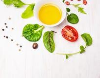 Sallad med dressingen, oliv och tomater på vitt trä arkivbild