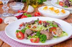 Sallad med feg lever, stekte champinjoner och tomater royaltyfri fotografi