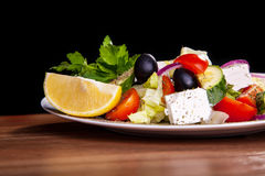 Sallad med fetaost, oliv, grönsallat, tomater, gurka, citron Royaltyfria Bilder