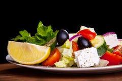 Sallad med fetaost, oliv, grönsallat, tomater, gurka, citron Arkivbild