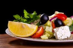 Sallad med fetaost, oliv, grönsallat, tomater, gurka, citron Fotografering för Bildbyråer
