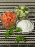 Sallad med gurkor, tomater och gräddfil, majonnäs Arkivfoto