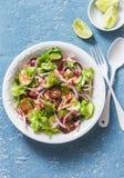 Sallad med kokt höna, tomater, gurkor, grönsallat, den röda löken och den kryddiga ranchdressingen på en blå bakgrund Fotografering för Bildbyråer