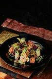 Sallad med lax-, räka-, grönsallat-, gurka- och sojabönagroddar i en svart platta arkivfoton