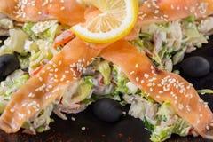 Sallad med laxen, grönsaker, citronen och svarta oliv på den svarta plattan isolerade den täta hörlurarbilden för black slapp övr Fotografering för Bildbyråer