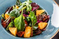Sallad med lever, arugula, apelsinen, spenat och mandlar p? plattan ?ver m?rkerstenyttersida sund begreppsmat Top besk?dar arkivfoton