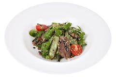 Sallad med nötkött för ruccola och thin snittpå rund maträtt arkivbild