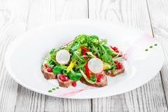 Sallad med nötköttbiff, behandla som ett barn spenat, grönsallat, söt peppar och korn av granatäpplet på träbakgrundsslut upp Arkivfoton