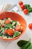 Sallad med pasta, spenat, tomater körsbär och ricotta på vit Arkivbilder