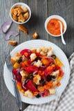 Sallad med peppar, tomater, lökar, oliv och krutonger med gammal träbakgrund för sousomna Royaltyfria Bilder